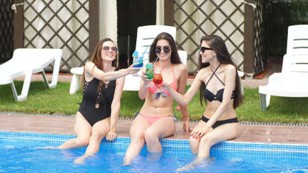 Three girl girlfriends met by the pool to celebrate a bachelorette party. Drink cocktails and have fun.