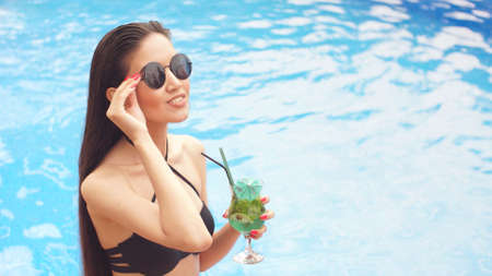 Portrait of glamorous brunette girl in sunglasses with cocktail in hands against the background of the pool. Фото со стока