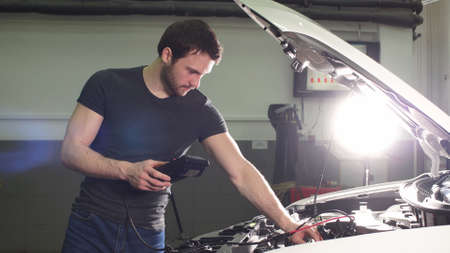 Auto Mechanic Is Checking Internal Faults in Important Car Systems and Robustness of Connections