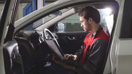 Young repairman, dressed in a work uniform, is in the car and checks the cars electronic system. Zdjęcie Seryjne