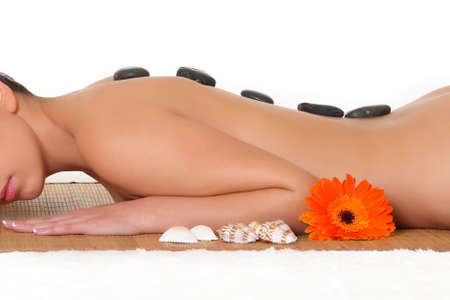 hot stone massage: Glowing young woman with hot stones on her back
