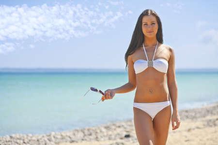 mujer joven en el mar en un bikini blanco Foto de archivo