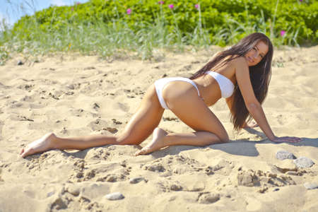 sexy girl in the sand in a white bikini photo