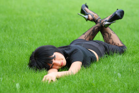 sexy beautiful woman with a tight-fitting black dress. lying on the grass photo