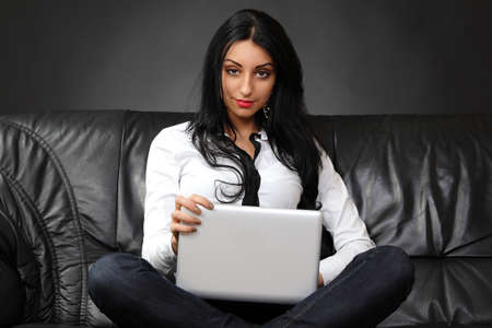 girl with a laptop on the sofa photo