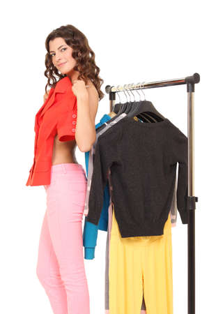 beautiful young girl chooses clothes in a wardrobe with hangers Stock Photo - 23908882
