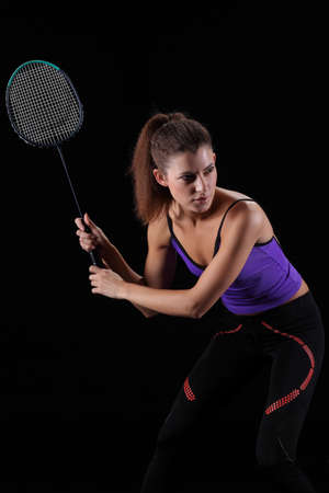 woman with badminton racket isolated on black photo