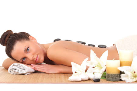 sexual chakra: Beautiful relaxing woman with stones on her back in a Spa