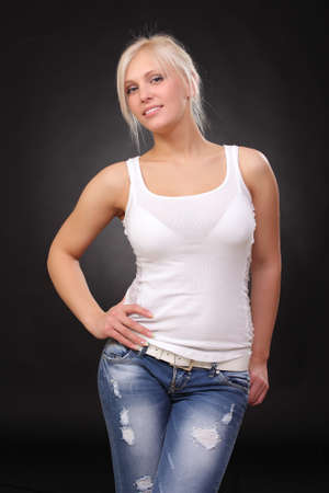 a young blonde wearing jeans and a tank top. on a black background
