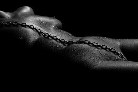 Female naked body with drops of water and chain
