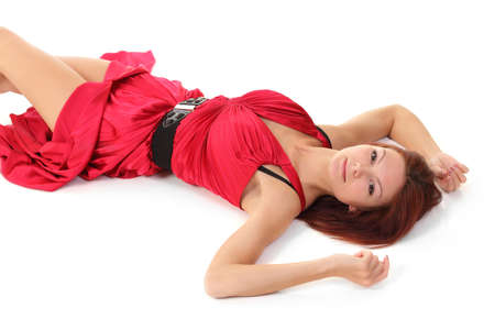 young girl lies on a white background in a red dress Stock Photo