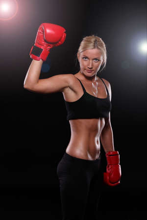 Young woman wearing boxing gloves isolated on black photo