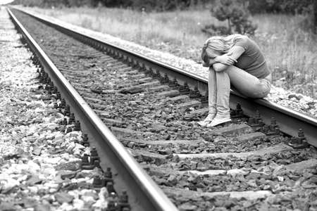 upset girl sitting on the rails