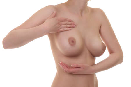 Young woman examining her breasts for signs of breast cancer