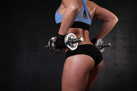 image of sexy woman holding dumbbells from behind photo