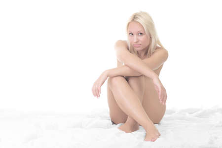Beautiful naked woman on a blanket, isolated on a white photo