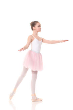school age girl playing dress up wearing a ballet tutu, isolated on white photo