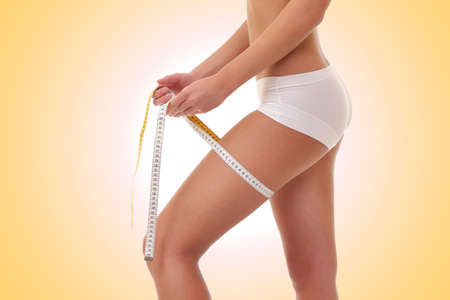 metric: She is measuring her thigh with a yellow metric tape measure Stock Photo