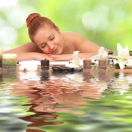 young healthy girl relaxing in spa. reflected in water photo
