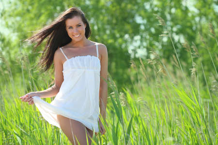 young woman in a white dress in the grass photo