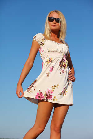 oliva: girl in a ping dress and sunglasses on background of sky
