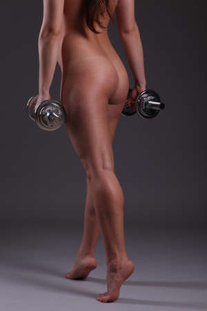 flexing: beautiful sports girl with dumbbells