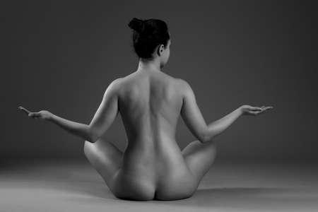 mujer desnuda sentada: Joven y bella mujer practicando yoga desnuda