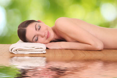 naked woman back: beautiful young girl lying in a spa