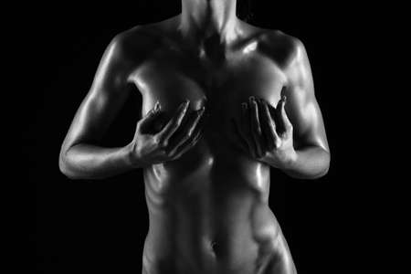 female nudity: naked female body on a black background