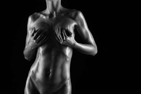 erotic breast: naked female body on a black background