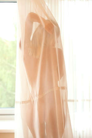 Nude girl behind a curtain at the window