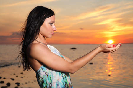 sun worship: Free woman enjoying freedom feeling happy at beach at sunset.
