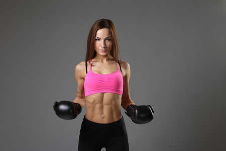 girl with boxing gloves  on a gray background