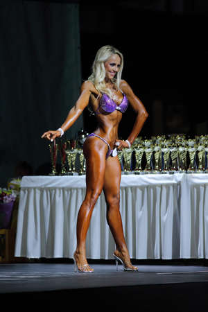 muscled: Slim muscled woman . Fitness bikini on stage