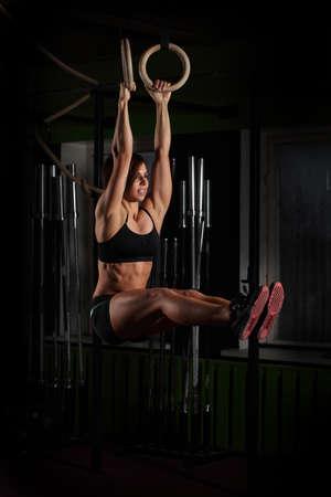 gymnastik: Fit junge Frau auf Turner Ringe in der Turnhalle