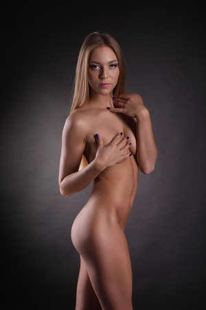 tetas: El cuerpo desnudo de la chica hermosa sobre fondo oscuro