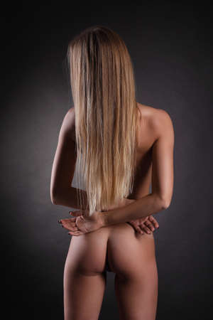 Beautiful back of a nude young woman with long blond hair