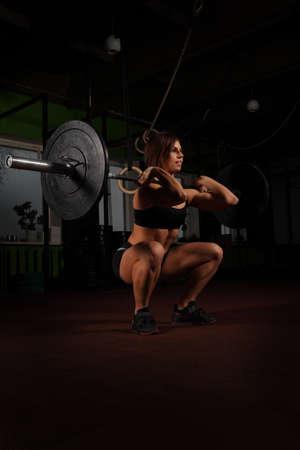 Mujer de levantamiento de pesas en el gimnasio