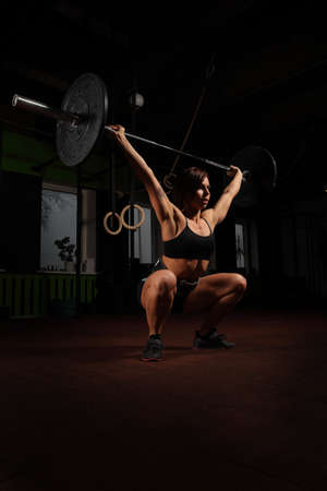 jerk: Woman lifting weight in gym