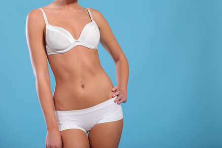 woman measuring waist: young woman measuring waist on blue background Stock Photo