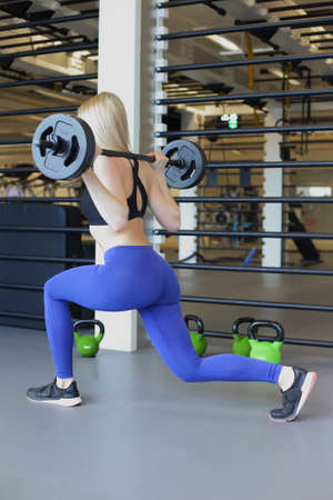 Fit girl doing lunges with a barbell 스톡 콘텐츠