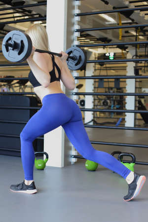 girl squatting: Fit girl doing lunges with a barbell Stock Photo