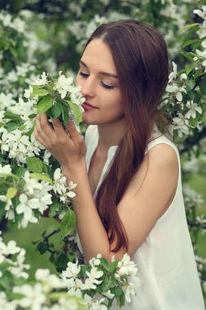 Portrait of beautiful woman in the flowered garden