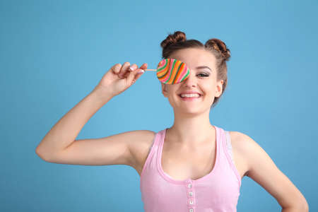 Young happy girl with colored candy on a blue background