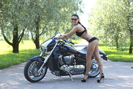 sexy young woman in a black bikini with a motorcycle