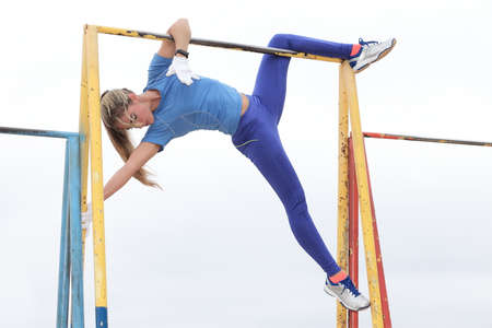 Sexy and young girl practicing on the horizontal bar Stock Photo