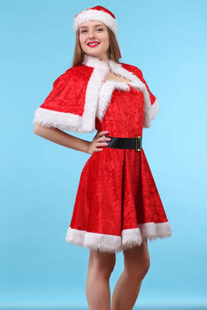 female sexuality: Beautiful sexy girl in a Christmas suit posing on a blue background