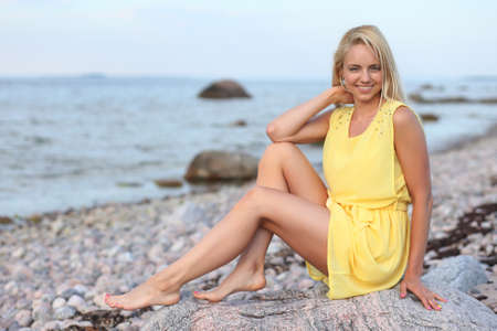 Beautiful blonde girl in a yellow dress on the beach Stock Photo