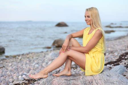 Hermosa chica rubia en un vestido amarillo en la playa