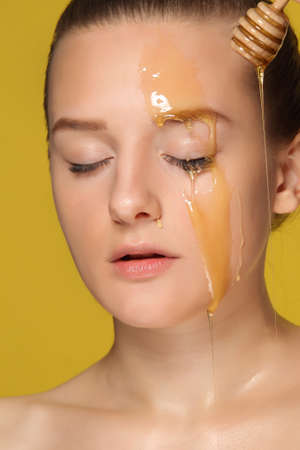 renew.: Beautiful young woman with honey on her face